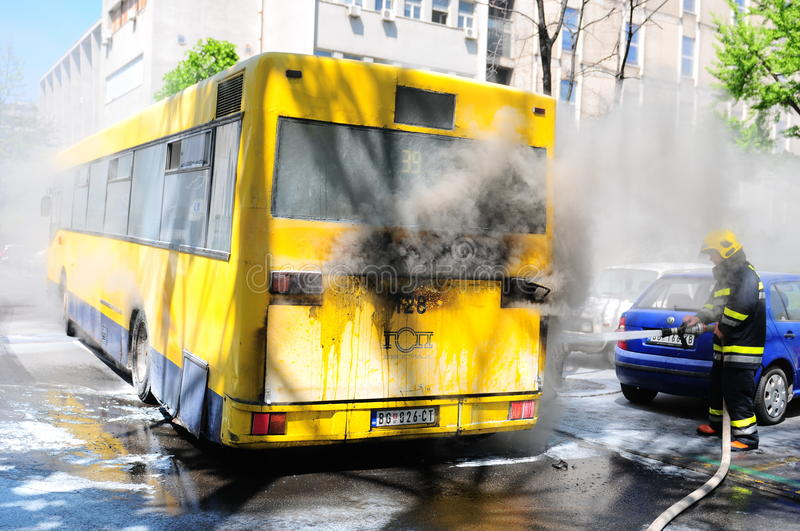 Bus on fire on the street in the middle of the day. SERBIA, BELGRADE - APRIL 27, 2012: Bus on fire on the street in the middle of the day. More than have of the stock photo
