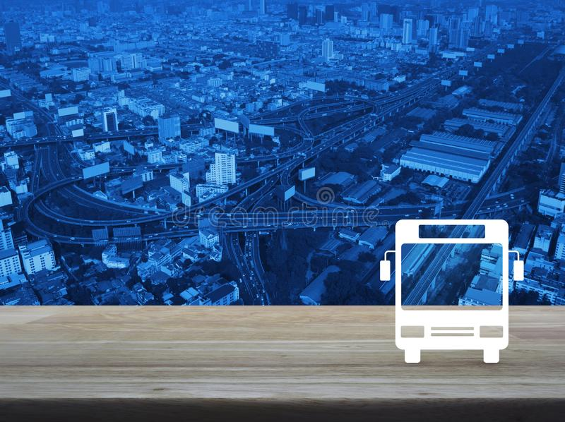 Business transportation bus service concept. Bus flat icon on wooden table over modern city tower, street and expressway, Business transportation service concept royalty free stock photo