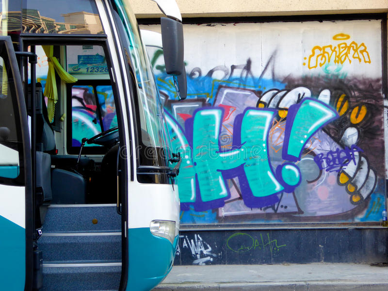 Bus in the front of Graffiti wall. A bus parked in the front of Colorful graffiti drawn on the wall on Moganshan road in Shanghai China royalty free stock photos