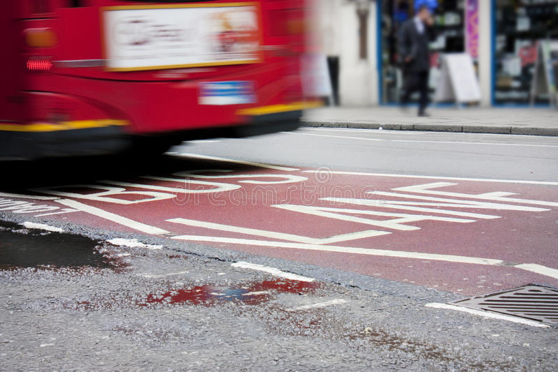 Bus lane in london. With red bus crossing over the sign royalty free stock photo
