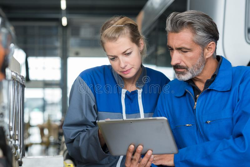 Bus mechanics looking at tablet. Bus stock images