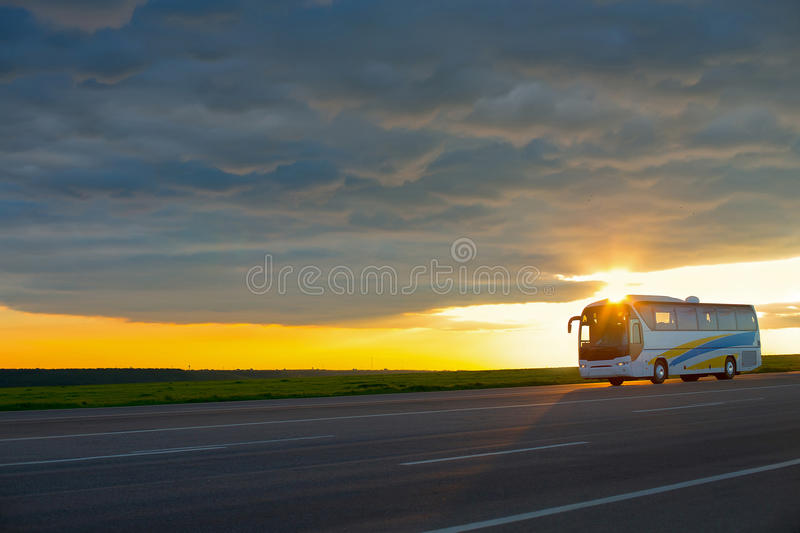 Bus moving on high-speed highway at sunset. stock photos