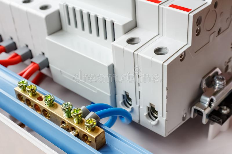 Bus neutrale collegato dal primo piano blu dei cavi contro gli interruttori automatici nella scatola di montaggio di plastica bia immagini stock libere da diritti