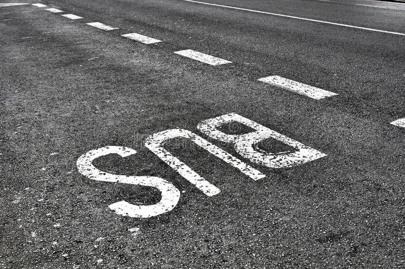Bus sign on tarmac road. Bus lane sign painted on to tarmac road royalty free stock photography