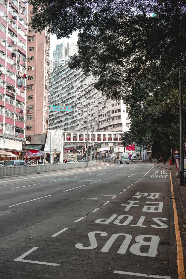 Bus stop on an empty street in Hong Kong with large residential building in the background royalty free stock image