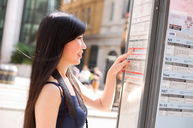 Bus stop. Japanese lady at the bus stop checking the schedule royalty free stock images