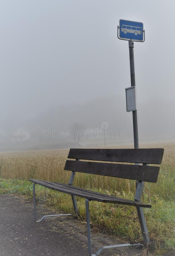 Bus stop in the middle of nowhere. Foggy morning gives the impression that this rural bus stop is in the middle of nowhere, tragic, waiting, sad, autumn, delay royalty free stock images