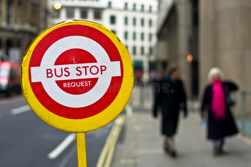 Bus Stop Request. A temporary bus stop sign in central London, with two people walking on the sidewalk in the background royalty free stock photo