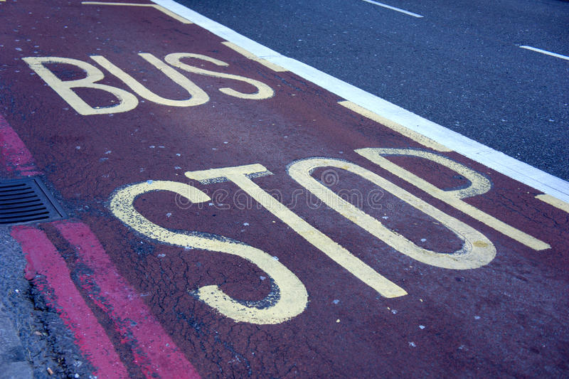 Bus stop sign. Painted on red bus lane stock photo