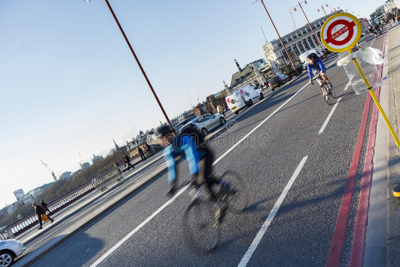 Bus Stop sign on the Blackfriars Bridge, cyclists in the background stock images