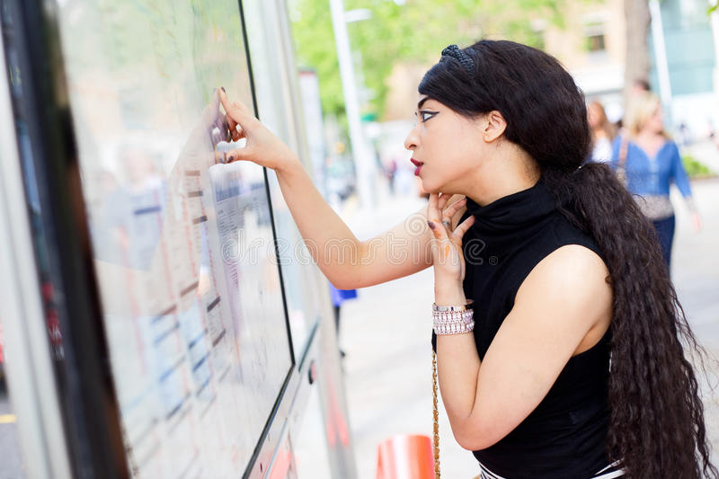 Bus stop. Young woman checking the timetable at the bus stop stock photography