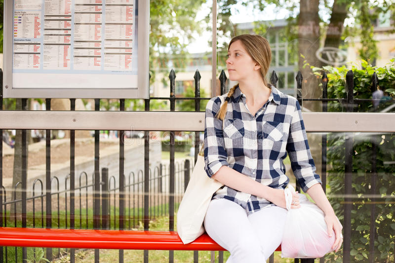 Bus stop. Young woman sitting at the bus stop royalty free stock photos