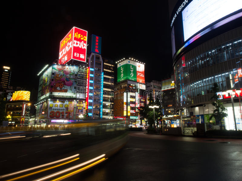 A bus streaks past Tokyo Neon Signs. A bus streaks past neon signs in Tokyo. Just having rained, the road has a sheen of water reflecting the coloured lights of stock photo