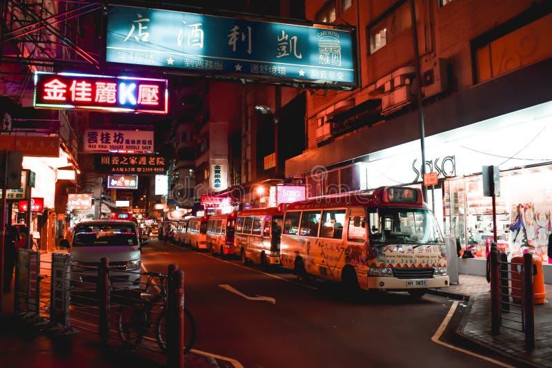 Bus vuoti che riposano sotto le insegne nella sera su una via di Hong Kong immagine stock