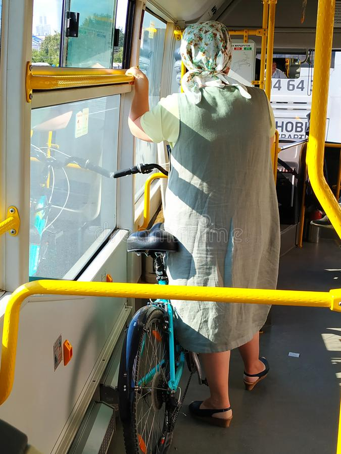 The bus is a woman, she holds a blue bike. Dressed in a long summer gray dress, head scarf, shoes with heels. Rear view. The bus h royalty free stock photos