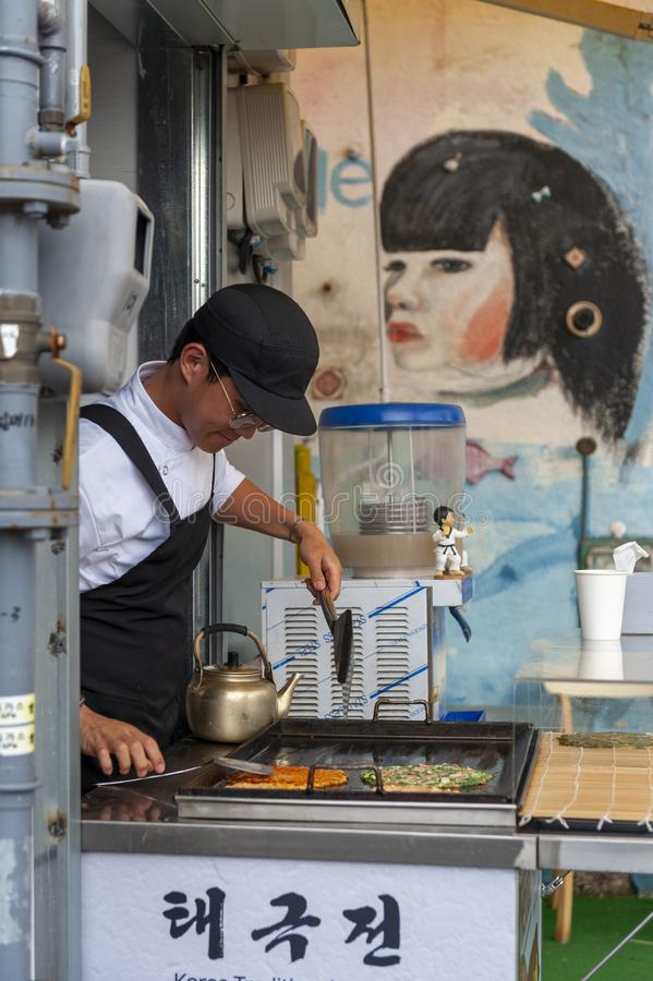 Young man vendor cooking Buchimgae or Korean pancake in Gamcheon Culture Village in Busan, South Korea royalty free stock images