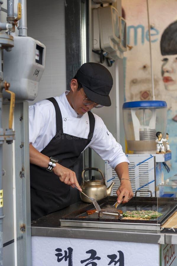 Young man vendor cooking Buchimgae or Korean pancake in Gamcheon Culture Village in Busan, South Korea stock photo