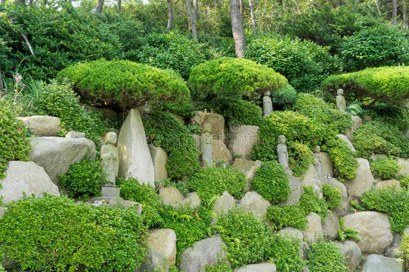 Chinese priest stone sculptures in the garden of Haedong Yonggungsa Temple. BUSAN, SOUTH KOREA - JULY 20, 2017 : Chinese priest stone sculptures in the garden of stock photo