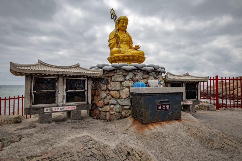One buddha at Yonggungsa temple. BUSAN, SOUTH KOREA - JUNE 9, 2019: Buddha at Yonggungsa temple on a cloudy summer afternoon stock image