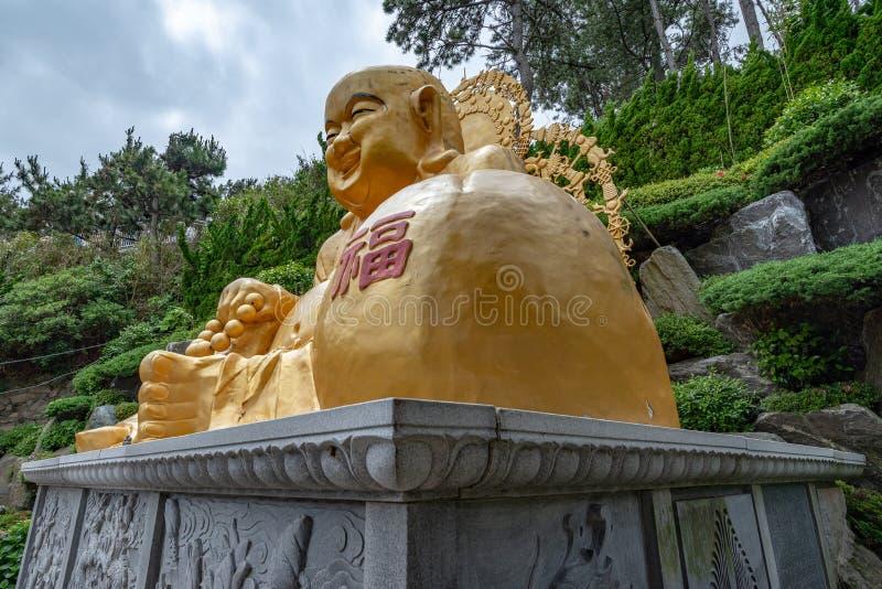 Laughing buddha at Yonggungsa temple. BUSAN, SOUTH KOREA - JUNE 9, 2019: Laughing Buddha at Yonggungsa temple on a cloudy summer afternoon royalty free stock photography