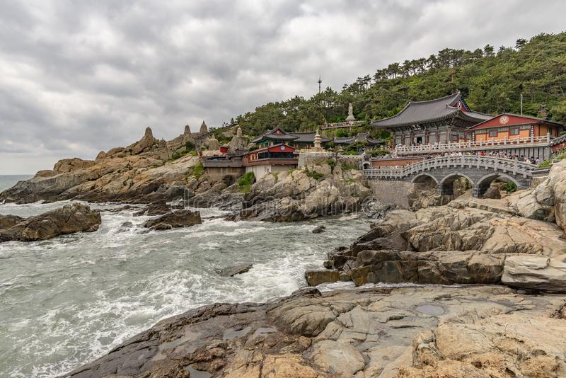 Yonggungsa temple seen from the sea. BUSAN, SOUTH KOREA - JUNE 9, 2019: Yonggungsa temple seen from the sea on a cloudy summer afternoon royalty free stock image