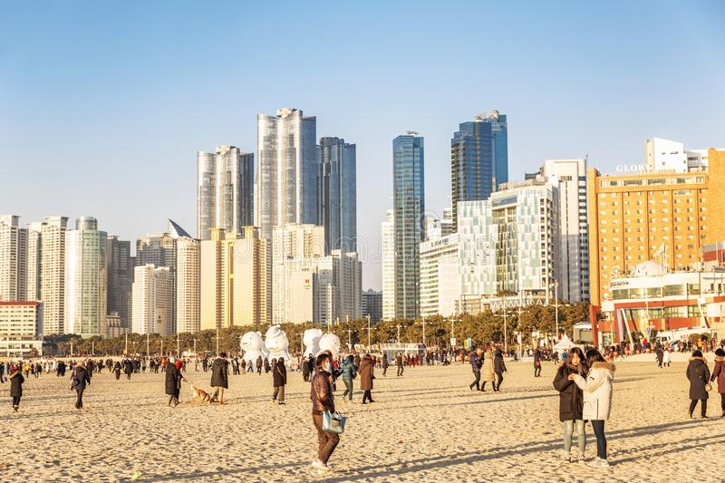 Busan, South Korea, 01/01/2018: People walk on a sandy beach in winter. New Year celebration royalty free stock images