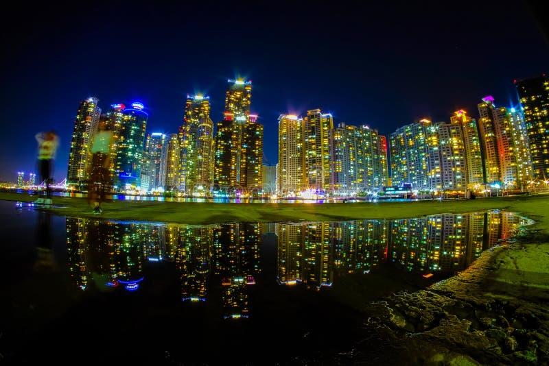 Busancityscape bij nacht met bezinning bij Haeundae-strand stock fotografie