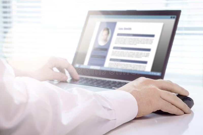 Buscador y candidato de trabajo que escriben su curriculum vitae y CV con el ordenador portátil imagen de archivo