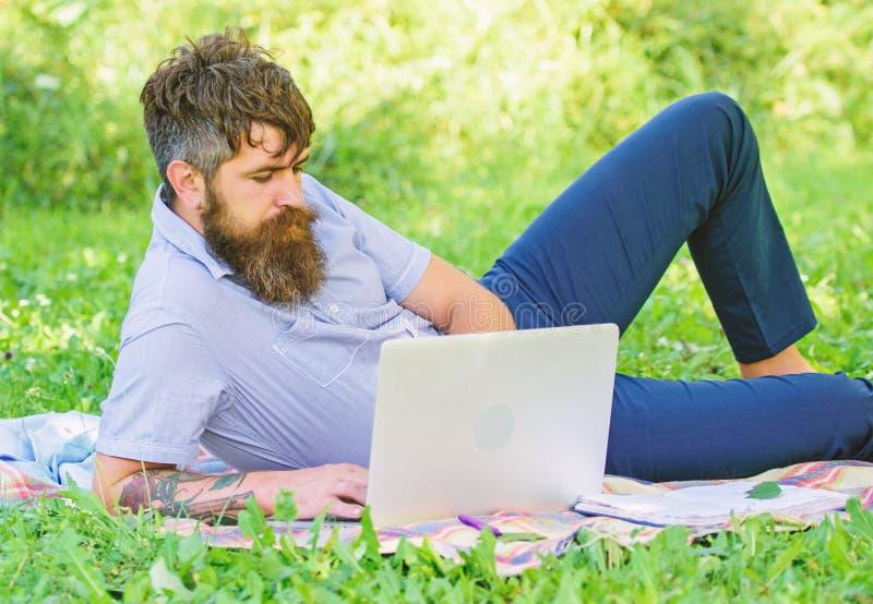 Buscar la inspiraci?n Hombre barbudo con el fondo de relajaci?n de la naturaleza del prado del ordenador port?til Programa de esc fotografía de archivo libre de regalías