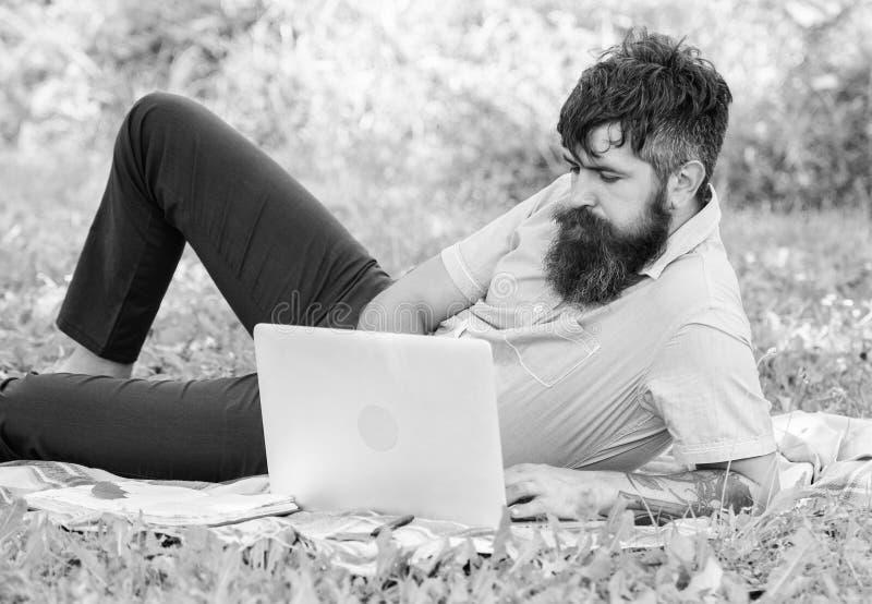 Buscar la inspiraci?n Hombre barbudo con el fondo de relajaci?n de la naturaleza del prado del ordenador port?til Programa de esc foto de archivo
