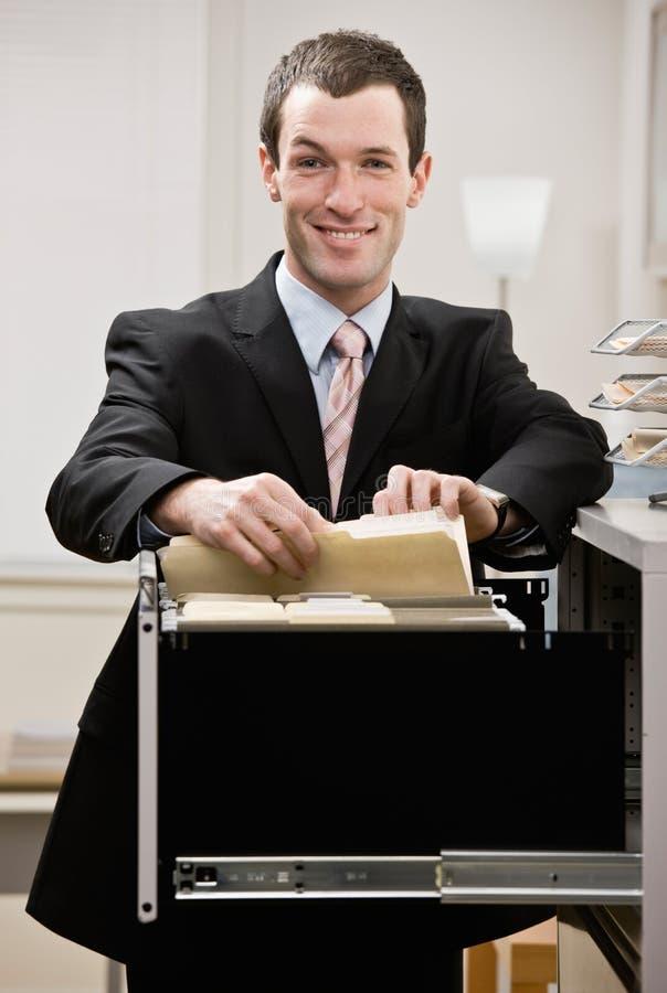 Buscas confiáveis do homem de negócios através da gaveta de arquivo foto de stock