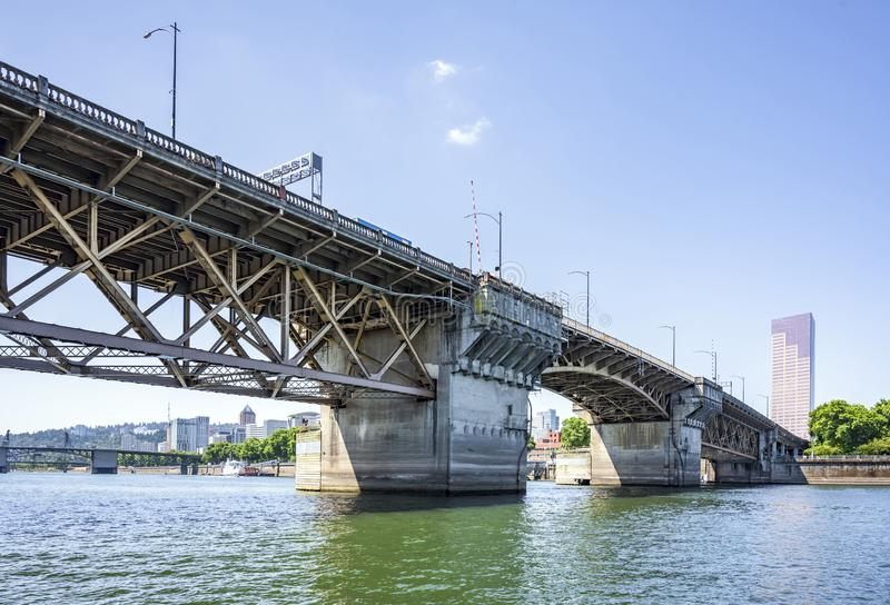 Buscle Burnside Bridge with big support columns and truss roadbed across Willamette River in Portland Oregon. Wide transportation Burnside drawbridge over the royalty free stock image