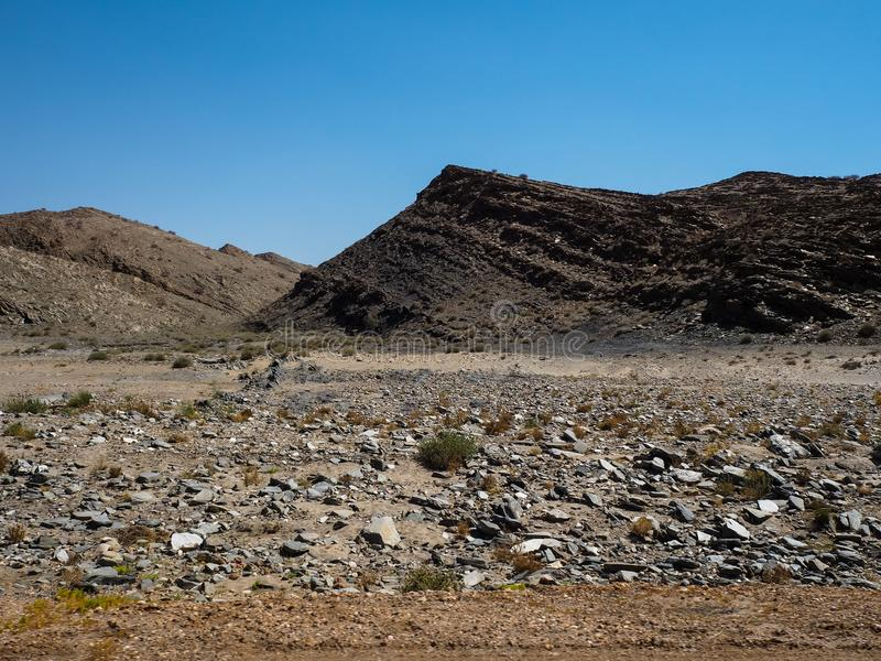 Busen vaggar jordning för bergtorkalandskapet av unik geografi för den Namib öknen med den blixtrande stenen och deserterar den g arkivbild