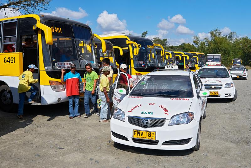 Buses and taxis in a row at the Tagbak Bus Terminal. Iloilo City, Iloilo Province, Philippines: Buses and taxis in a row together with passengers at the Tagbak stock image