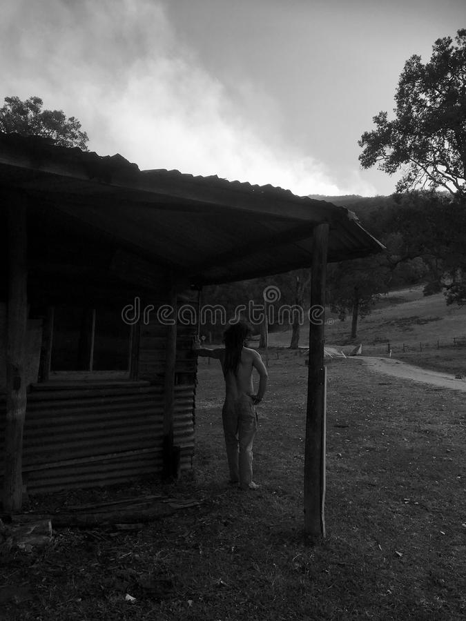 Bush man looking toward smoke in distance. Black and white image of topless bush man, leaning against olden day type cabin looking toward smoke off in distance royalty free stock photo