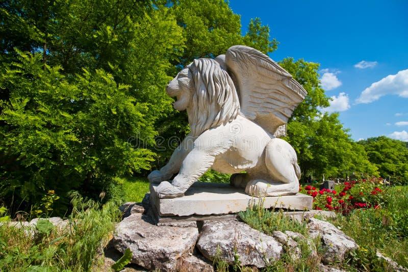 Winged Lion of Saint Mark modern symbolic sculpture, symbolizing evangelist St Mark, on stone pedestal. Busha, Ukraine - 09.06. 2019: winged Lion of Saint Mark royalty free stock image