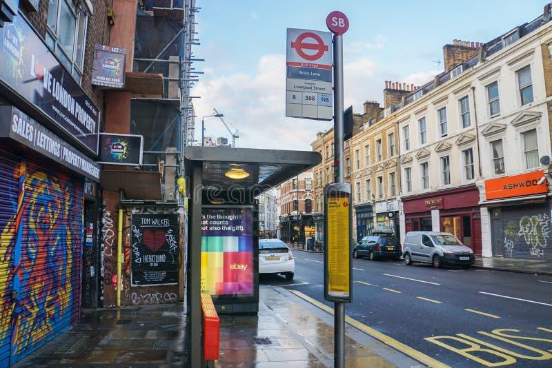 Bushaltestelle am Ziegelstein-Weg mit Weinlesegebäudehintergrund in London lizenzfreie stockbilder