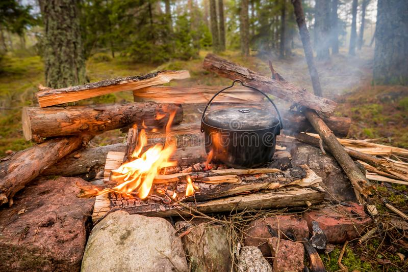 Bushcraft setting with a camping pot on a burning fire. A camping kettle is standing on a burning fire with a reflector in the background made from firewood stock image
