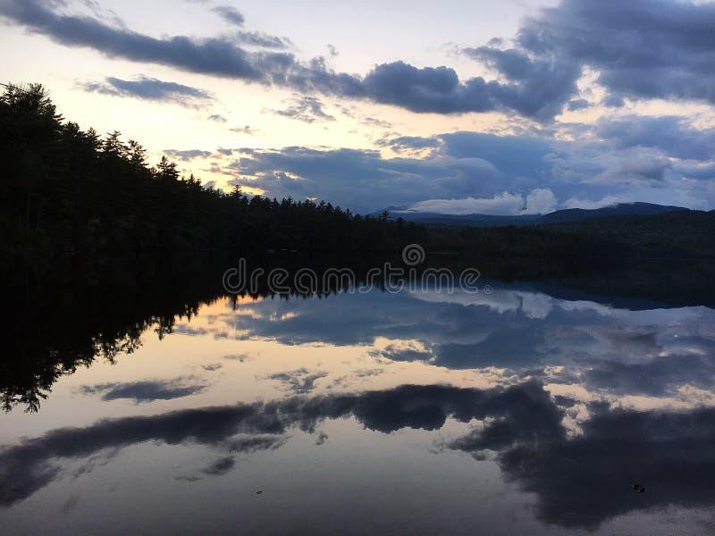 bushers镇定垂直构成湖moutain反射的反映日落的结构树 库存图片