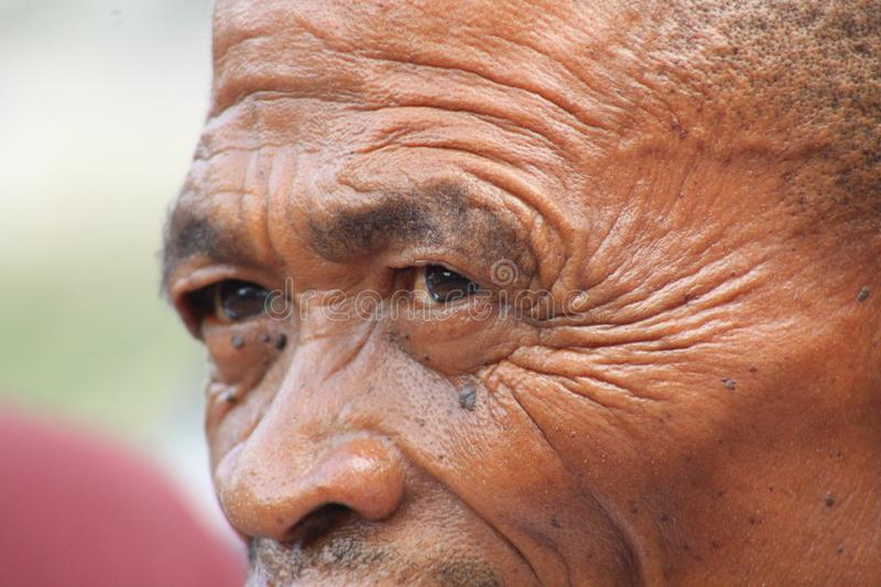 Bushman hunter portrait. A close-up portrait of an old hunter Bushman with wrinkles. Hunter-gatherer peoples of Southern Africa royalty free stock photo