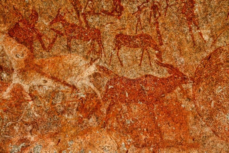 Bushmen rock painting of human figures and antelopes, giraffe of the Matopos National Park, Zimbabwe royalty free stock photos