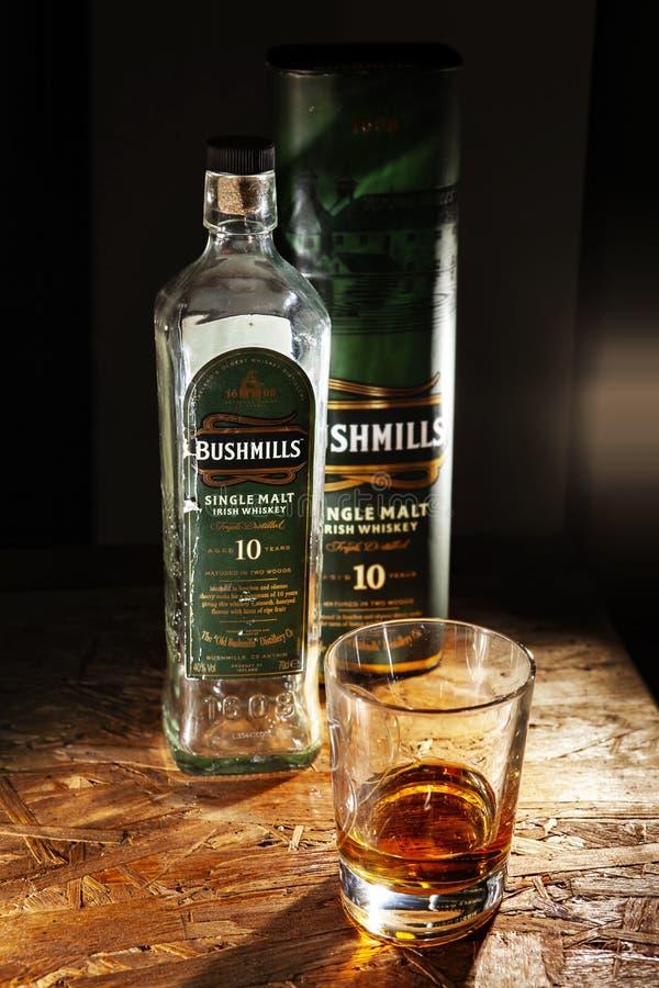 Bushmills single malt whisky. LVIV, UKRAINE - DECEMBER 04: Bottle of Bushmills whisky and glass on wooden shelf on December 04, 2017 in Lviv stock photo