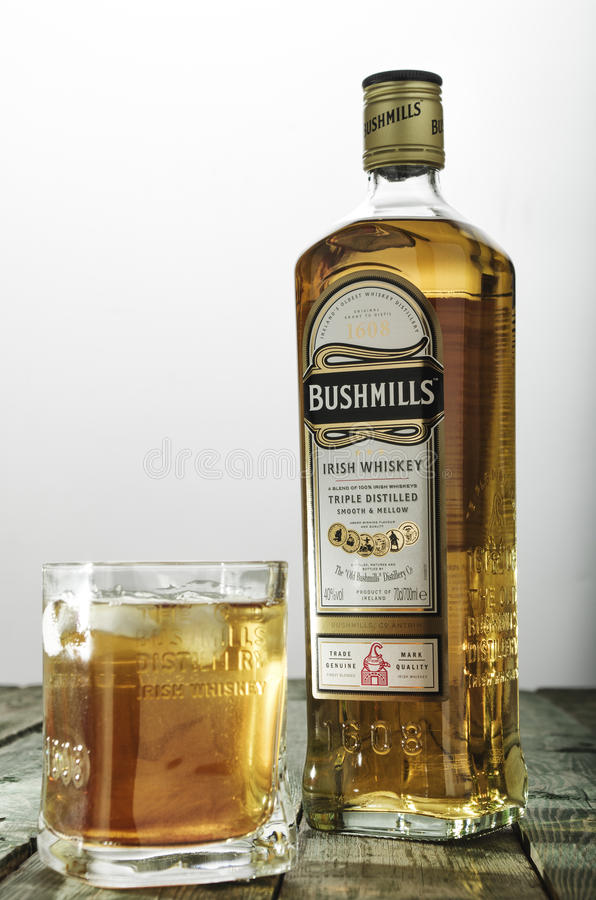 Bushmills whiskey glass and bottle on green wooden table. MINSK, BELARUS - MARCH 10, 2017: Bushmills whiskey glass and bottle on green wooden table. Bushmills is stock image
