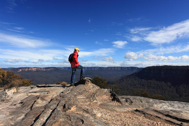 Bushwalker admiring the view from Flat Rock Wentworth Falls. A bushwalker admires the views of Narrow Neck, Mt Solitary and the gangerangs from Flat Rock stock image
