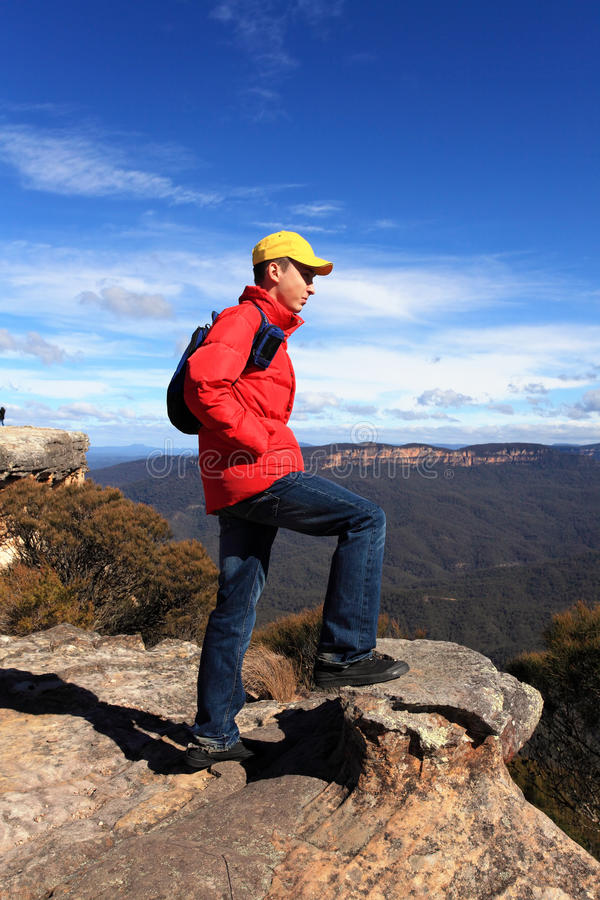 Bushwalker hiker looking out over mountain valley views. A bushwalker hiker looks out at views to Kings Tableland and Jamison Valley from Flat Rock Blue royalty free stock image