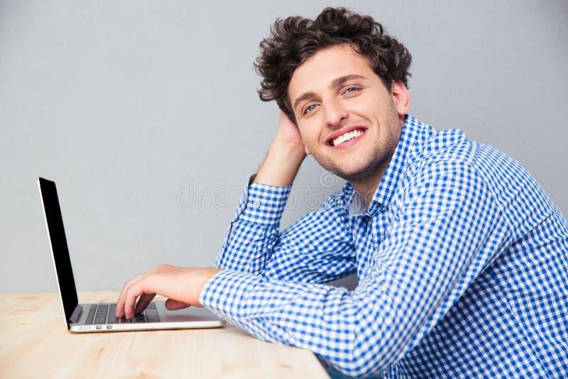 Busienssman de sorriso que senta-se na tabela com portátil foto de stock royalty free