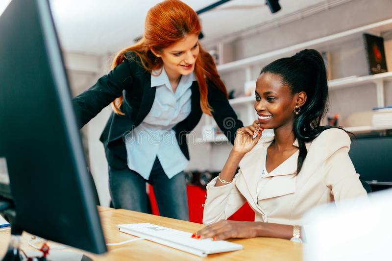 Busiensswoman advising colleague. In office during work stock photo