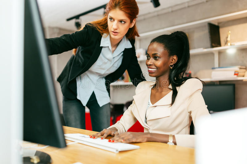 Busiensswoman advising colleague. In office during work royalty free stock photography
