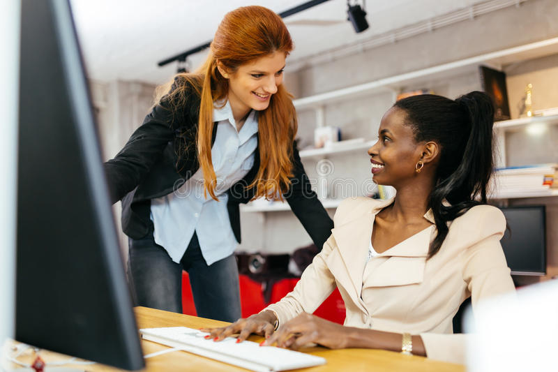 Busiensswoman advising colleague. In office during work royalty free stock photo