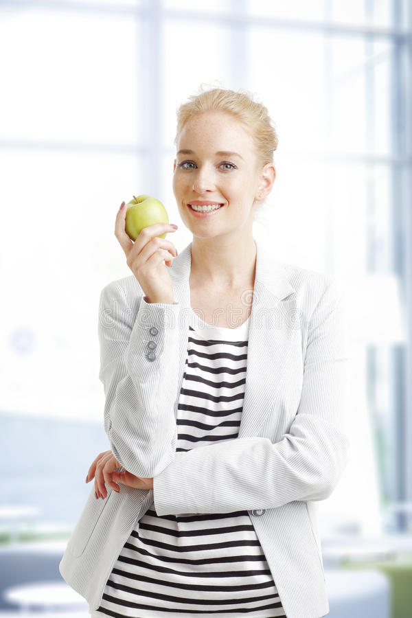 Busiensswoman with apple. Portrait of young businesswoman standing at office while holding hands green apple royalty free stock image